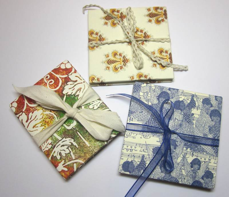 Three books made from card and scraps of paper.
